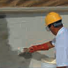 A man priming a area of wall